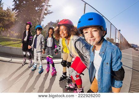 Big group of multiethnic boys and girls, roller skaters in safety helmets, holding hands standing in line at stadium outdoors