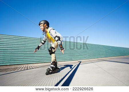 Side view portrait of preteen boy, roller skater in helmet and protective gear, skating fast at outdoor rollerdrome against blue sky
