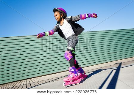 Side view portrait of African girl, active roller skater, riding fast at outdoor rollerdrom