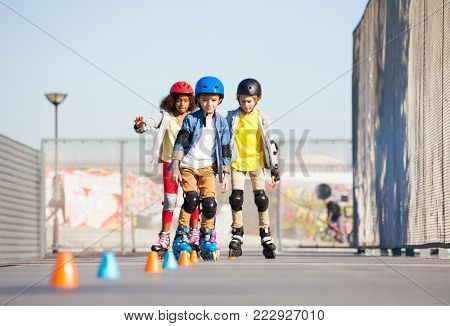 Portrait of multiethnic boys and girls, happy inline roller skaters exercising on slalom course in summer