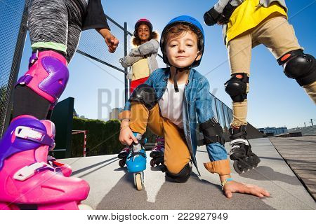 Portrait of cute schoolboy in safety gear on roller skates outdoors