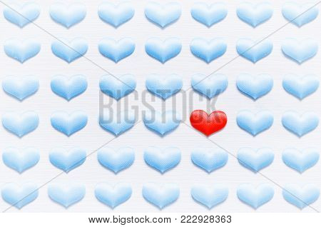 Heat care cardiology concept. Red heart on the white background among blue hearts, shallow DOF. Cardiology and heart health care concept. Cardiology and heart care background