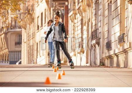 Portrait of happy teenage girl roller skating around the cones at city side walk