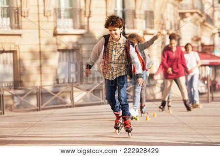 Portrait of happy teenage boy roller skating at city side walk