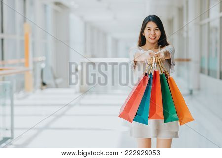 Young Asian woman carrying and presenting colorful shopping bags while walking in shopping mall. focus on the hand