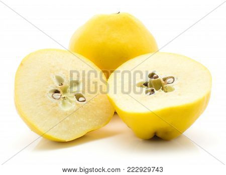 One quince and two cut halves isolated on white background raw yellow with seeds