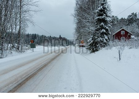 traffic sign with 80 kilometer per hour and a red wooden house in Varmland Sweden