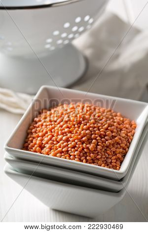 Raw red, dried  lentils in white bowl with sieve on kitchen table