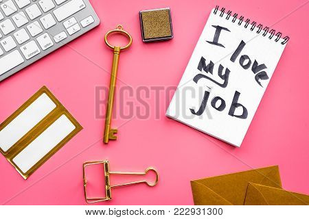 Happy at work. Handwritten motto I love my job in notebook near stationery on pink background top view.