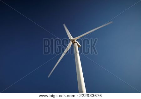 Wind power generation, Wind turbine against blue sky at sunny day