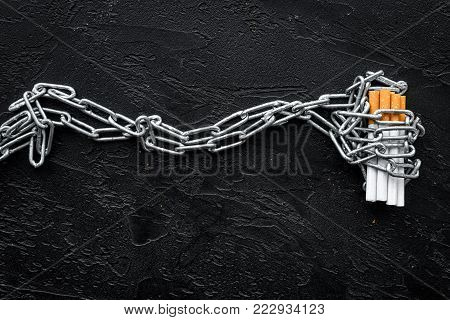 Quit smoking. Cigarettes in chains on black background top view.
