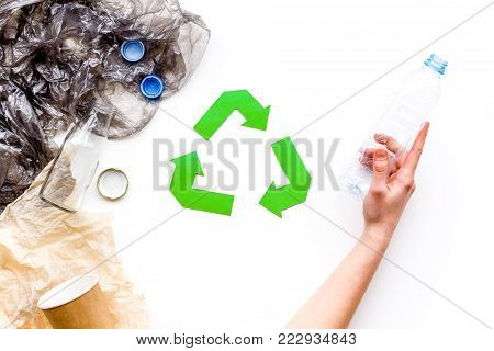 Sorting waste and recycle. Green paper recycling sign among waste paper, plastic, glass, polyethylene on white background top view.