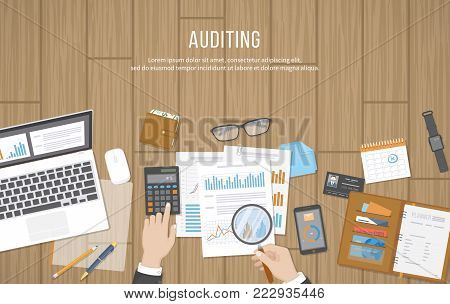 Auditing concepts. Auditor inspects assessing financial documents. Businessman hands with magnifying glass above documents, graphics, charts. Research, planning, accounting, analysis, calculation.