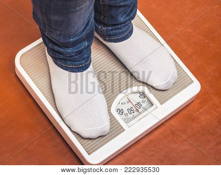 a young girl who leads a healthy way of life, stands on the scales and measures her weight