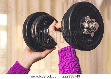 a young girl does sports, she lifted a heavy dumbbell