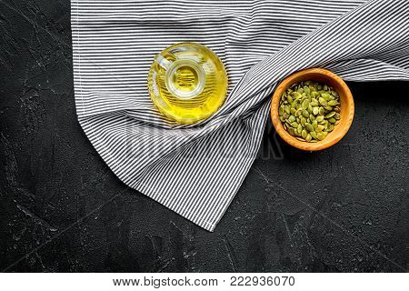 Use seed oil as cosmetics. pumpkin seed oil in jar near pumpkin seed in bowl on blue tablecloth on black background top view.