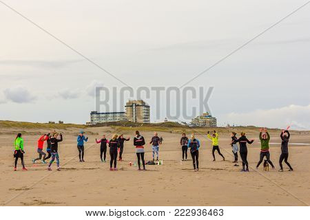 Kijkduin, The Hague, the Netherlands - 21 January 2018: women traing on the beach with Kijkduin resort in background