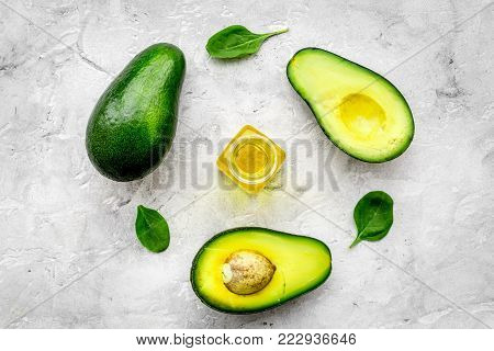Vegetable oil as cosmetics. Avocado oil in bottles near sliced avocado on grey background top view.