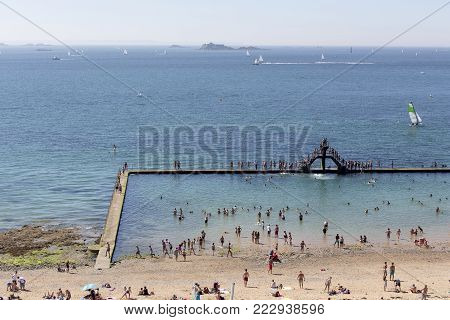 Saint Malo, France - August 16, 2016: The Plage de Bon Secours is at the western side of the intra-muros of St-Malo, in France. This beach has a saltwater pool with people swimming