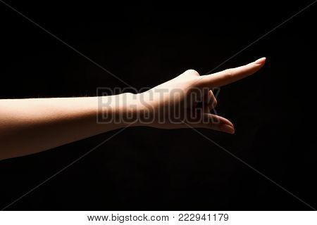 Female hand, thumb-side view, forefinger pointing away. Hand gestures - woman indicating on virtual object with index finger, isolated on black background, copy space