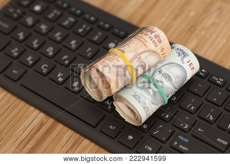 Roll of Indian Currency Rupee Notes on computer keyboard on wooden background