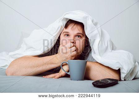 man watchin horror movie under the blanket at home