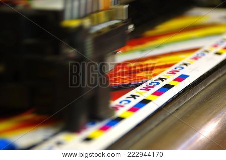 Printing head creates CMYK test and image on paper. Colorful large plotter printer machine.