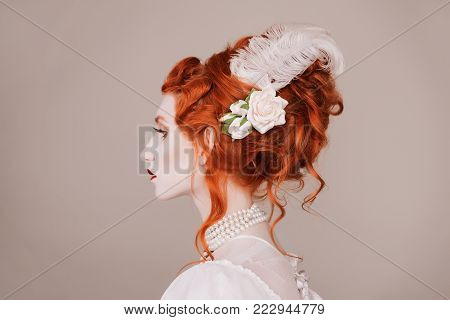 Elegant style of the girl. Retro style. Hairstyle in vintage style. Look of a girl in a renaissance style. Women's style. Red-haired woman in white dress with pale skin and luxury hair style on gray background.