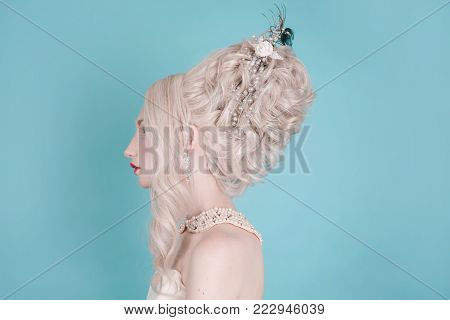 A woman with hairdo and white hair. Blonde girl with hairdo and pale skin and blue eyes with bright unusual appearance. Retro model with hairdo. Copyspace. Stylish hairdo. Blonde woman with beautiful luxurious rococo hairdo
