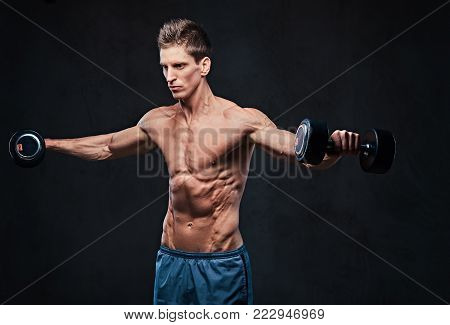 Shirtless athletic male doing shoulders lateral head exercises with dumbbells.