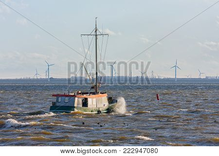 Dutch fishing ship at lake ijsselmeer with wind turbines at the horizon