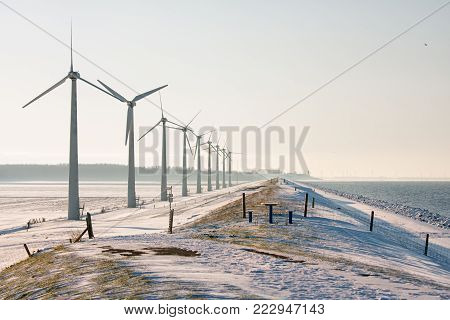 Dutch winter landscape with snowy fields and wind turbines aolong a dike. At the horizon the skyline of fishing village Urk