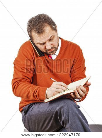 Mature businessman talking on the phone and writing information in notebook