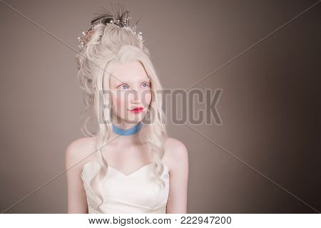 Young model on a gray background. Blonde model with a luxurious hairdo. Stylish model in retro dress. Model with natural make-up. A blonde model with a beautiful luxurious rococo style hairdo in a white dress with a blue ribbon