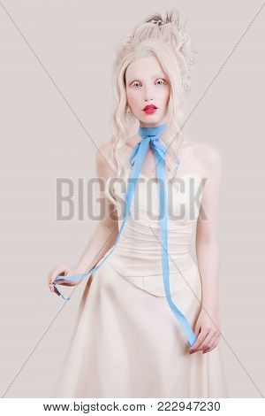 Young model on a gray background. Blonde model with a luxurious hairdo. Stylish model in retro dress. Model with natural make-up. A blonde model with a beautiful luxurious hairdo in white dress with ribbon around neck