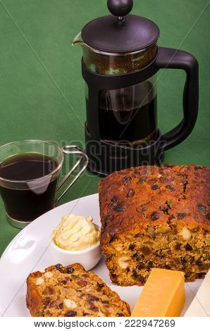 Irish Stout Fruitcake with a slice cut and two pieces of cheese and a portion of butter.