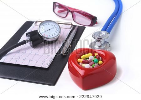 Red heart, asorted pils, glasses and a stethoscope on white background