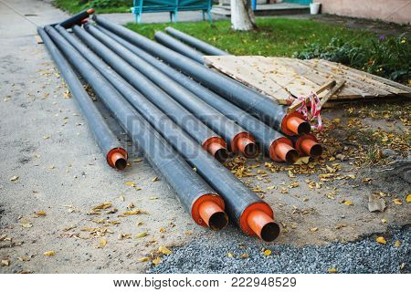 Water pipes with insulation lie on the ground. Construction works. Water pipes with insulation lie on the ground. Construction works. Water pipes with insulation lie on the grass. Water pipes industry. Heavy industry. The industry of pipes. Metal industry