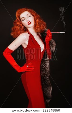 A model in stylish clothes. A stylish woman. Girl with a stylish hairstyle. Young stylish woman. Red-haired stylish woman with curly hair in red stylish dress and long gloves smoke on black background.