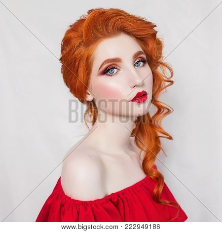 Young model on a gray background. Blonde model with a luxurious hairdo. Stylish model in retro dress. Model with natural make-up. Beautiful red-haired model in red dress. Portrait of a model with red hair