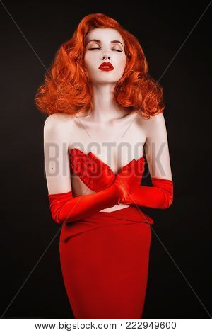 A model in stylish clothes. A stylish woman. Girl with a stylish hairstyle. Young stylish woman. Red-haired stylish woman with curly hair in red stylish dress
