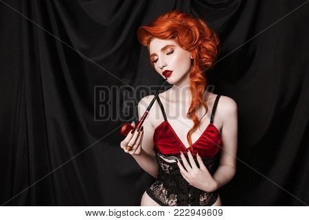 A model in stylish clothes. A stylish woman. Girl with a stylish hairstyle. Young stylish woman. Model in a stylish dress. A red-haired stylish woman with curly hair looks in a black corset
