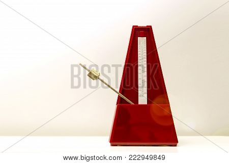 Mechanical metronome of red color on a white background with a light in the upper left corner