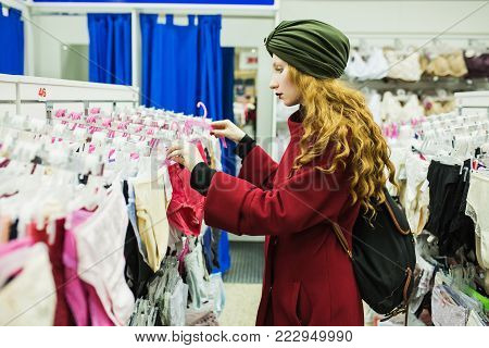 Red-haired girl with long hair picks underwear. The girl in the store. Stylish woman in the store. Make purchases in the big store. Clothing store. Shopping in a modern store