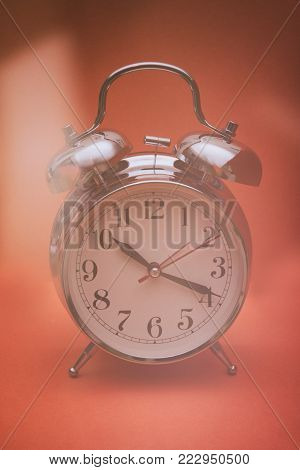 White retro clock isolated against an orange background with a vintage look
