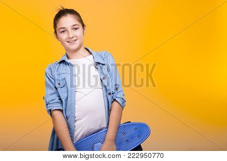 Young teeanger girl holding a blue skateboard in her hands on yellow background