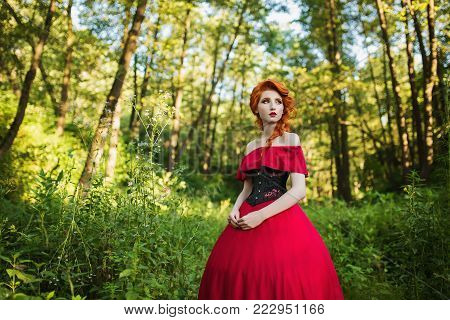 Beautiful red-haired girl in a red dress and in black corset. Beautiful red-haired girl in a red dress and in black corset. Fairy in the forest. Fairy in retro dress. Beautiful fairy from a fairy tale. A young fairy with a beautiful hairdo. Fairy on a fai