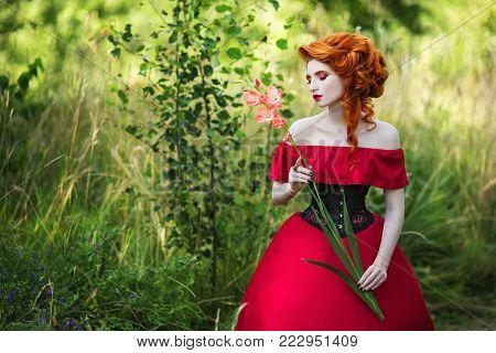 Beautiful red-haired girl in a red dress and in black corset. Fairy in the forest. Fairy in retro dress. Beautiful fairy from a fairy tale. A young fairy with a beautiful hairdo. Fairy on a fairytale background poster