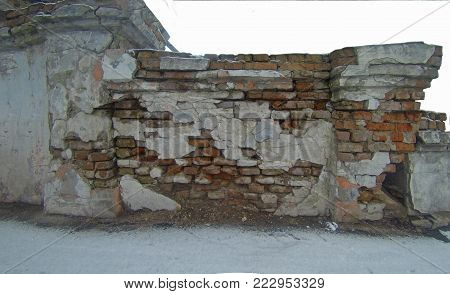 Piece of a ruined brick old wall. Ruins of the old city. Photo of an abandoned building for the post-apocalyptic theme.