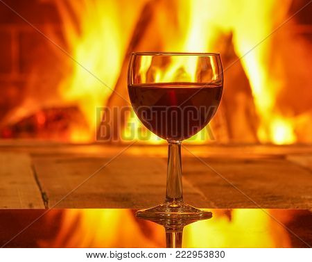 Glass of red wine against cozy fireplace background, winter vacation, winter vacation, in country house, horizontal.